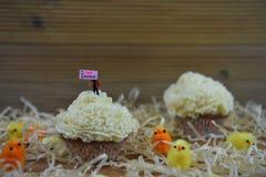 Petit gâteau avec la figurine miniature de personne jugeant un signe indiquant l'amour Pâques d'I entouré par des décorations Photo libre de droits