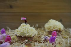 Petit gâteau avec la figurine miniature de personne jugeant un signe indiquant l'amour Pâques d'I entouré par des décorations Images stock