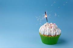 Petit gâteau avec le cierge magique sur un fond bleu image libre de droits