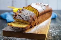 Petit gâteau avec le citron arrosé avec la poudre de sucre sur le conseil photo stock