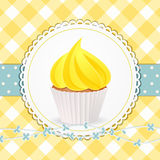 Petit gâteau avec le glaçage jaune sur le fond jaune de guingan Photographie stock
