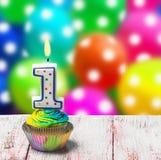 Petit gâteau avec le numéro un sur le fond des ballons Image libre de droits