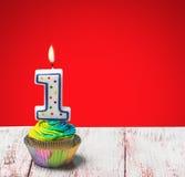 Petit gâteau avec le numéro un sur un fond bleu Images stock