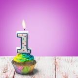 Petit gâteau avec le numéro un sur un fond pourpre Photo libre de droits