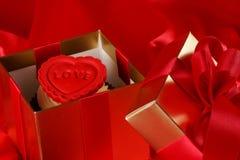 Petit gâteau avec un coeur rouge sur le dessus dans des cadres de cadeaux sur le dos rouge de satin Photos libres de droits