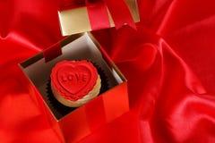 Petit gâteau avec un coeur rouge sur le dessus dans des cadres de cadeaux sur le dos rouge de satin Image libre de droits