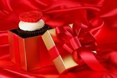 Petit gâteau avec un coeur rouge sur le dessus dans des cadres de cadeaux sur le dos rouge de satin Photo stock