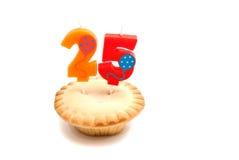 Petit gâteau avec vingt-cinq ans de bougie d'anniversaire sur le blanc Images stock