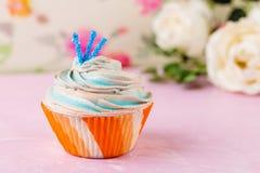 Petit gâteau bleu dans la tasse orange Images stock