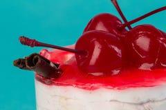Petit gâteau coloré avec une cerise sur le dessus Image stock