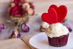 Petit gâteau décoré de deux coeurs rouges d'un plat blanc aux pages d'un livre ouvert Image libre de droits