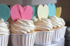 Petit gâteau décoré du givrage et des coeurs de sucre. Photos libres de droits