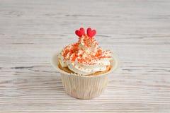 Petit gâteau décoré du sucre rouge et du décor culinaire de deux coeurs Photos libres de droits