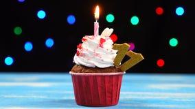 Petit gâteau délicieux d'anniversaire avec la bougie et le numéro brûlants 11 sur le fond brouillé multicolore de lumières banque de vidéos