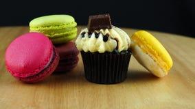 Petit gâteau délicieux de chocolat et macarons multicolores sur un conseil en bois brun banque de vidéos