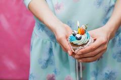 Petit gâteau d'anniversaire avec la seule bougie dans des mains femelles Photos stock