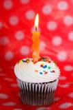 Petit gâteau de chocolat avec la bougie ondulée orange photographie stock