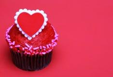 Petit gâteau de chocolat avec le coeur rouge sur le dessus, au-dessus du fond rouge Photo libre de droits