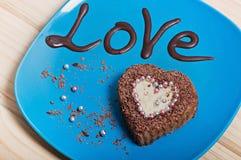 Petit gâteau de chocolat sous forme de coeur d'un plat bleu avec l'amour d'inscription Photo stock