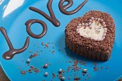 Petit gâteau de chocolat sous forme de coeur d'un plat bleu avec l'amour d'inscription Photo libre de droits