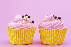 Petit gâteau de deux bonbons avec des boules de chocolat sur un backgr rose Images stock