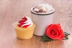Petit gâteau de fraise avec une tasse de chocolat chaud et d'une rose lumineuse de rouge Images stock