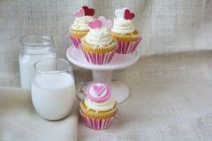 Petit gâteau de vanille de fondant de coeur et verre de lait Photo stock