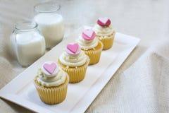 Petit gâteau de vanille de fondant de coeur et verre de lait Images libres de droits