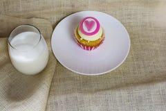 Petit gâteau de vanille et verre de lait Image stock