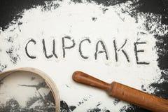 Petit gâteau de Word écrit sur la farine dispersée, un fond noir image libre de droits