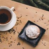 Petit gâteau fait maison avec du sucre en poudre d'un plat noir et d'une tasse blanche de thé avec les additifs naturels sur un p photographie stock libre de droits