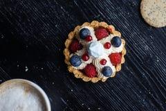Petit gâteau fait maison avec les baies de myrtilles, crèmes et fraîches sur le fond en bois photographie stock libre de droits