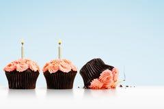 Petit gâteau heurté dans la rangée des petits gâteaux avec des bougies sur le bleu Image libre de droits