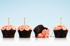 Petit gâteau laissé tomber dans la rangée des petits gâteaux avec des bougies sur le bleu Photographie stock libre de droits