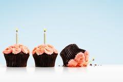 Petit gâteau laissé tomber dans la rangée des petits gâteaux avec des bougies sur le bleu Image stock