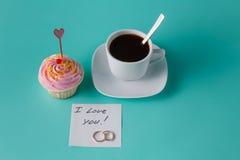 Petit gâteau rose coloré sur le fond bleu vert avec la tasse de café Images stock