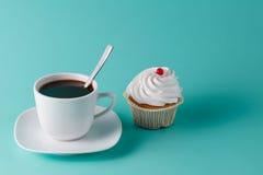Petit gâteau rose coloré sur le fond bleu vert avec la tasse de café Photo stock