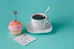 Petit gâteau rose coloré sur le fond bleu vert avec la tasse de café Photo libre de droits
