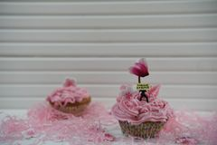 Petit gâteau rose de printemps décoré d'une figurine miniature de personne tenant un signe avec le ressort de mots bonjour et cyc Image stock