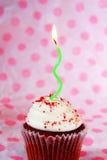 Petit gâteau rouge de velours avec la bougie ondulée verte images libres de droits