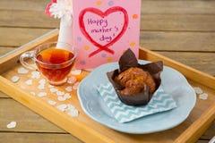 Petit gâteau, thé, vase à fleur et carte de voeux heureuse de jour de mères dans le plateau Images stock