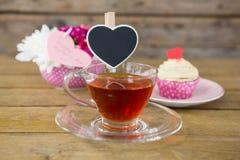 Petit gâteau, thé, vase à fleur et carte de voeux heureuse de jour de mères dans le plateau Images libres de droits