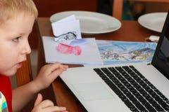 Petit garçon à l'aide de l'ordinateur portable jouant des jeux photo libre de droits