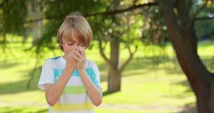 Petit garçon à l'aide de son inhalateur dans le parc banque de vidéos