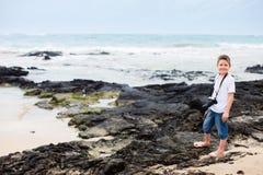 Petit garçon à la côte rocheuse Image stock