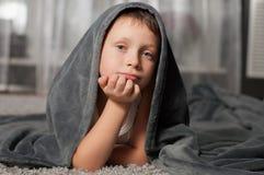Petit garçon à la maison sur le tapis Image libre de droits