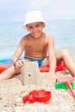 Petit garçon à la plage tropicale faisant le château de sable Photographie stock libre de droits