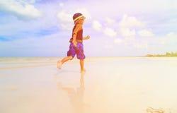 Petit garçon éclaboussant l'eau sur la plage tropicale Photos libres de droits