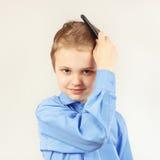 Petit garçon élégant dans la chemise lumineuse se brossant les cheveux une brosse à cheveux Photographie stock libre de droits