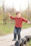 Petit garçon équilibrant sur de vieux pneus Photo libre de droits